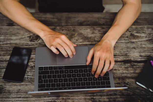 Hands doing transcription services on Laptop